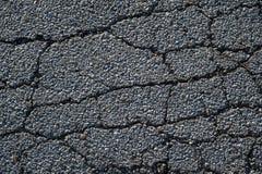 Barsten in asfalt op een straat stock afbeelding