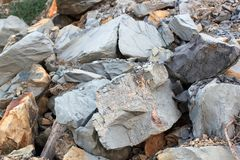 Barsten en kleurrijke lagen van zandsteenachtergrond Een grote hoop van zandsteen, bergruimte van divers natuurlijk zandsteen Pat Stock Afbeelding