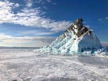 Barsten op de oppervlakte van het blauwe ijs Bevroren meer Baikal in de winterbergen Het sneeuwt De heuvels van pijnbomen Karpati stock afbeeldingen