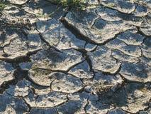 Barsten toe te schrijven aan droog klimaat Droog grasgras op harde droge klei stock afbeelding