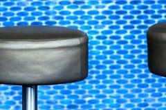 Barstool de cuero negro moderno delante de empañado, vigoroso-azul foto de archivo