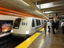 BART pociąg przyśpiesza w stacyjną platformę z ludźmi czeka i Obrazy Stock