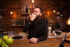 Bartende, das hinter dem Tresen köstlichen grünen Apfel entgegengesetzt isst lizenzfreies stockfoto