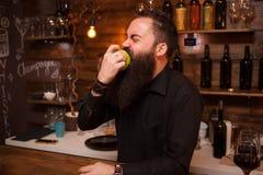Bartende, das hinter dem Tresen köstlichen grünen Apfel entgegengesetzt isst stockbild