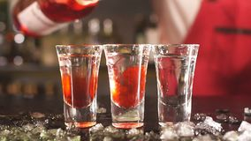 Bartender που προσθέτει το κόκκινο ποτό στο γυαλί κοκτέιλ στο μετρητή φραγμών απόθεμα βίντεο