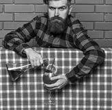 bartender έννοια Μπάρμαν με τη μακριά γενειάδα και mustache και μοντέρνη τρίχα στο ακριβές μπουκάλι εκμετάλλευσης προσώπου, χύνον στοκ φωτογραφία με δικαίωμα ελεύθερης χρήσης