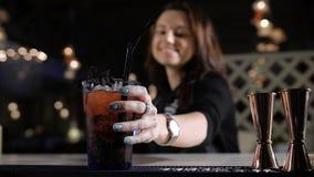 Bartender βάζει ένα αποκλειστικό κοκτέιλ για το ελκυστικό brunette Καλά χιούμορ και γέλιο στο φραγμό φιλμ μικρού μήκους