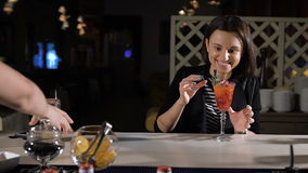 Bartender βάζει ένα αποκλειστικό κοκτέιλ για το ελκυστικό brunette Καλά χιούμορ και γέλιο στο φραγμό απόθεμα βίντεο