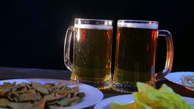 Bartender βάζει στον πίνακα με τα πρόχειρα φαγητά σε ένα μαύρο υπόβαθρο δύο τις πλήρεις κούπες της αφρίζοντας μπύρας απόθεμα βίντεο