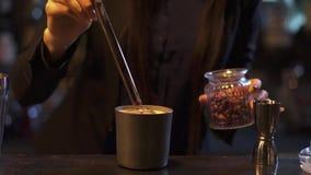 Bartender γυναίκα που κάνει τη διακόσμηση του φλυτζανιού μετάλλων με το ποτό με τα ξηρά rosebuts απόθεμα βίντεο