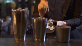 Bartender γυναικών που έχει το μεγάλο κομμάτι του πάγου στο χέρι και την κοπή της αυτό με το ειδικό αιχμηρό δίκρανο για να κάνει  φιλμ μικρού μήκους