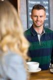 Bartender εξυπηρετώντας καφές στη γυναίκα στον καφέ Στοκ Φωτογραφίες