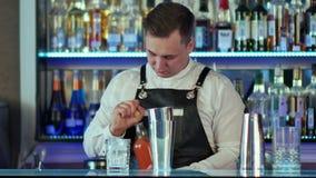 Bartender κάνει ένα κοκτέιλ στο φραγμό, χύνει σε ένα ποτήρι από το δονητή απόθεμα βίντεο