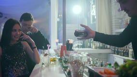Bartender κάνει τα τεχνάσματα με το ποτό για τους χαμογελώντας πελάτες πίσω από το μετρητή φραγμών στο νυχτερινό κέντρο διασκέδασ φιλμ μικρού μήκους