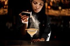 Bartender κορίτσι που κρατά έναν δονητή καρυκευμάτων προσθέτοντας γεύσεις στις εύγευστες κοκτέιλ στοκ φωτογραφία
