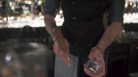 Bartender με τη δερματοστιξία hipster που τσιμπεί τον πάγο για τα coctails με τον παγοθραύστη στο υπόβαθρο του σύγχρονου φραγμού  απόθεμα βίντεο