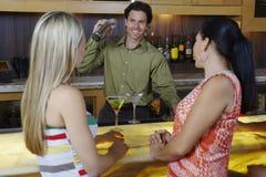 Bartender που αναμιγνύει τα ποτά για τις γυναίκες στο φραγμό Στοκ Φωτογραφία