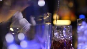 Bartender που αναμιγνύει τον πάγο και το ποτό με το κουτάλι φραγμών απόθεμα βίντεο