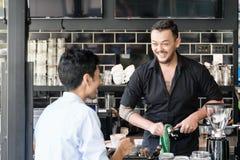 Bartender που καθαρίζει τη μηχανή espresso μιλώντας με τα cus Στοκ εικόνα με δικαίωμα ελεύθερης χρήσης