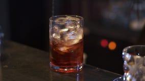 Bartender που κατασκευάζει το κοκτέιλ στο φραγμό κοντά επάνω Χέρι μπάρμαν που αναμιγνύει το οινόπνευμα με τους κύβους πάγου στο γ φιλμ μικρού μήκους