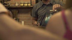 Bartender που κατασκευάζει το οινοπνευματώδες κοκτέιλ με τον πάγο και το μπλε ποτό στο μετρητή φραγμών στον καφέ Χύνοντας ποτό μπ απόθεμα βίντεο