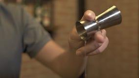 Bartender που κατασκευάζει το οινοπνευματώδες κοκτέιλ στο μετρητή φραγμών του εστιατορίου Χύνοντας ποτό μπάρμαν στο γυαλί προετοι απόθεμα βίντεο