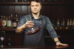 Bartender που μεταγγίζει το κρασί χωρίς διατάραξη του ιζήματος στοκ φωτογραφία με δικαίωμα ελεύθερης χρήσης