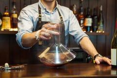 Bartender που μεταγγίζει το κρασί χωρίς διατάραξη του ιζήματος στοκ φωτογραφίες