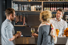 Bartender που μιλά με τους πελάτες στο μετρητή φραγμών Στοκ Φωτογραφίες