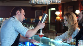 Bartender που προετοιμάζει το κοκτέιλ για ένα κορίτσι που ανυπομονεί να καθίσει στο φραγμό Στοκ Εικόνες