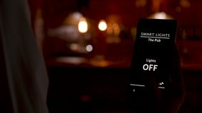 Bartender που χρησιμοποιεί μια έξυπνη εγχώρια εφαρμογή για να ανοιχτούν τα φω'τα απόθεμα βίντεο