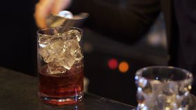 Bartender προετοιμάζει ένα εύγευστο οινοπνευματώδες κοκτέιλ Το χέρι bartender βάζει τους κύβους πάγου σε ένα ποτήρι του ουίσκυ κα απόθεμα βίντεο