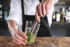 Bartender προετοιμάζει ένα κοκτέιλ χρησιμοποιώντας το madler στοκ εικόνα