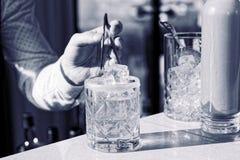 Bartender προσθέτει έναν κύβο πάγου στο κοκτέιλ, που τονίζεται Στοκ Εικόνες