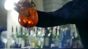Bartender προσθέτει το λεμόνι φετών και το πλαστικό άχυρο στο ποτό οινοπνεύματος με τους κύβους πάγου wineglass στην κινηματογράφ φιλμ μικρού μήκους
