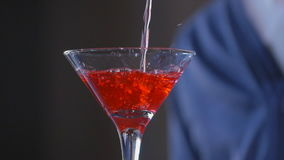Bartender χύνει ένα κόκκινο κοκτέιλ γυαλιού κοκτέιλ απόθεμα βίντεο