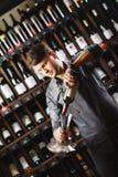 Bartender χύνει το κόκκινο κρασί στο διαφανές σκάφος στο κελάρι στοκ φωτογραφίες