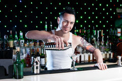 Bartender. Is pouring a drink and smiling Royalty Free Stock Images