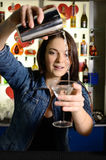 Bartender. Woman pours the cocktail into a glass Stock Images