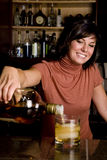Bartender. A pretty young bartender pouring a cold drink Stock Images