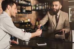Bartender accepting credit card at bar counter. Bartender accepting credit card at counter in bar. Cashless payment, modern technologies in every day life, copy stock photos