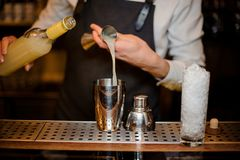 Bartender adding an alcoholic drink into a steel shaker. Bartender adding an alcoholic drink from a measuring cup into a steel shaker on the bar counter stock images