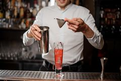 Bartender adding an alcoholic drink from the steel shaker through a sieve. Bartender adding an alcoholic drink from a steel shaker into a cocktail glass through royalty free stock photos