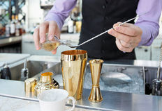 Bartender is adding ingredient in shaker. At bar counter royalty free stock photos