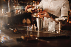 Bartender is adding ingredient in shaker at bar counter Royalty Free Stock Photos