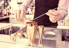 Bartender is adding ingredient in shaker, toned. Bartender is adding ingredient in shaker at bar counter, toned image Stock Photos