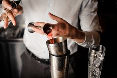 Bartender adding a red alcoholic drink into the steel shaker. Bartender adding a red alcoholic drink from the measuring cup into the steel cocktail shaker on the royalty free stock image