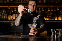 Bartender adding to an alcoholic drink in the glass an ice cube with splash. Bartender adding to an alcoholic drink in the glass an ice cube with tweezers with stock photography