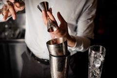 Bartender adding a transparent red alcoholic drink into the steel shaker. Bartender adding a transparent red alcoholic drink from the measuring cup into the stock photography
