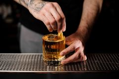 Bartender adds lemon zest in alcohol cocktail. Male tattooed bartender adds fresh lemon zest in cold alcohol cocktail with whiskey stock photography